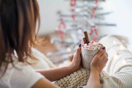 Young woman relax with cup of hot chocolate and marshmallows