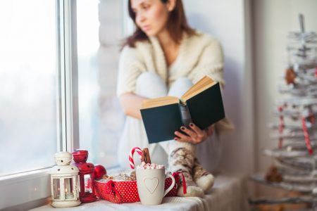 Thoughtful woman reading book in christmas decorated home